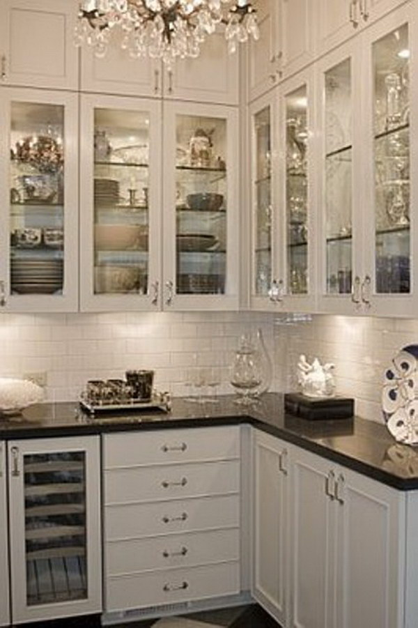 Black Countertops With Glass Cabinet Doors, Glass Shelves And Lighting.