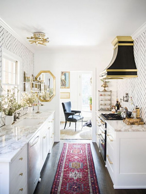 Mini White kitchen with Marble Countertops and black and gold hood over stove.