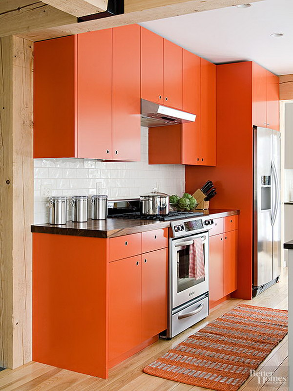Orange Kitchen Cabinets with Crisp Black Countertops and Shiny White Backsplash.