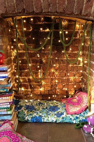 Turn a Fireplace Into a Nook With String Lights and Pillows.