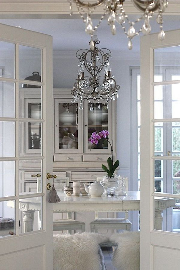 All White Dining Area With French Doors And Crystal Chandelier.