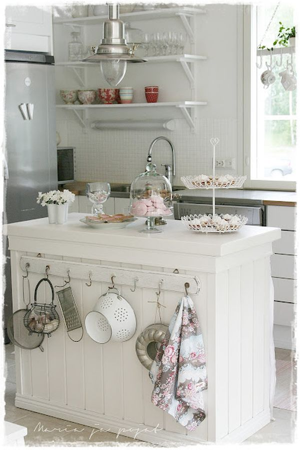 Shabby Chic Kitchen Island with Slightly Mismatched Hooks on One Side.