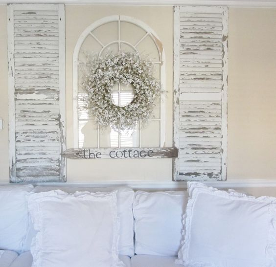 Turn Old Shutters and an Old Arch Window Into a Focal Point Over The Sofa.
