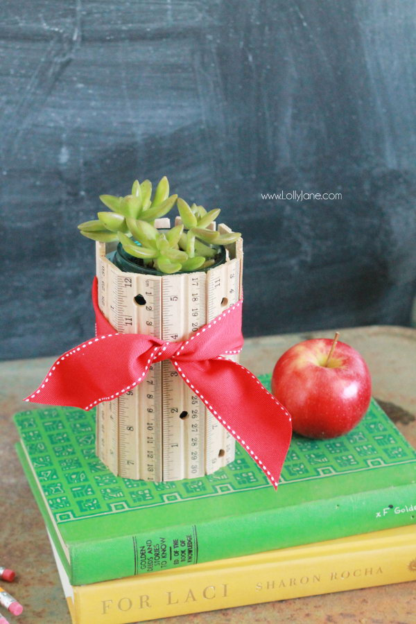 DIY Ruler Vase. Arrange the rulers with the same length in the shape of a vase, then tie with a red ribbon. It makes a perfect table centerpiece for your dinning room. See the detailes directions